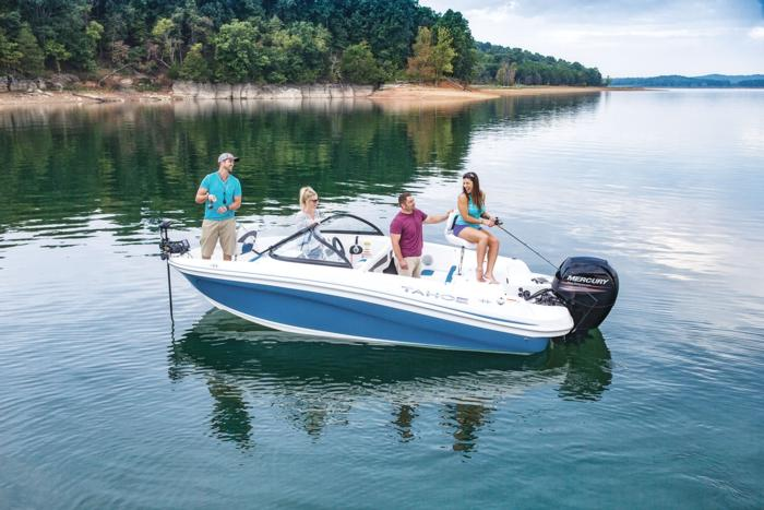 2019 Tahoe 450 TF fish and ski boat with trolling motor and Mercury outboard. People fishing from boat on lake.