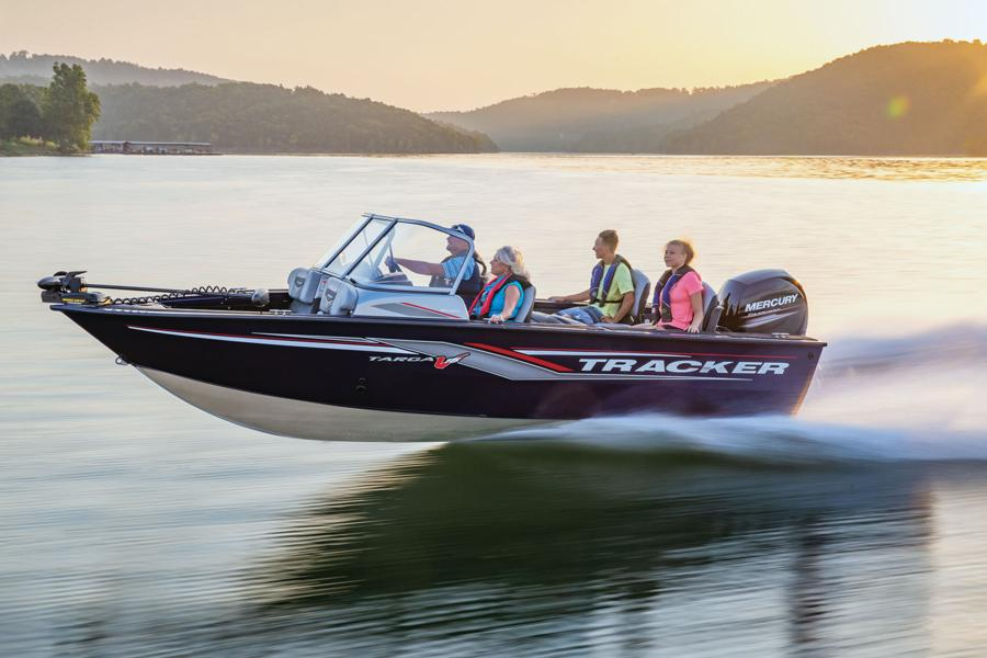 Four people on a Tracker Targa V-18 Combo cruising across picturesque lake with misty mountains in background